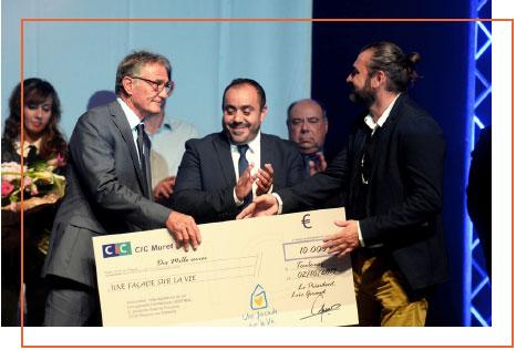 Remise de chèque effectuée par Guy NOVÈS au Président de l'association, Loïc GIRAUD